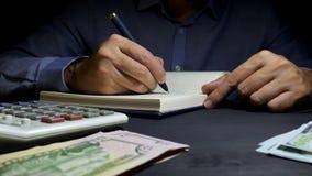 Escritura del contable en las figuras financieras del libro de cuentas Cálculo de negocio y finanzas caseras almacen de video