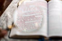 Escritura del 3:16 de Juan con las lupas de la lectura Fotos de archivo