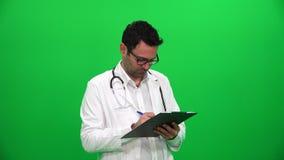 Escritura del doctor en el sujetapapeles almacen de metraje de vídeo