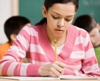 Escritura del estudiante en cuaderno en sala de clase de la escuela Imagen de archivo