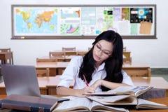 Escritura del estudiante en los libros en la sala de clase Imágenes de archivo libres de regalías