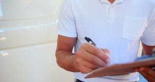 Escritura del hombre de entrega en el tablero almacen de video