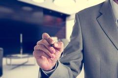 Escritura del hombre de negocios con un marcador en virtual Foto de archivo