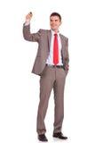 Escritura del hombre de negocios con una mano en bolsillo Imágenes de archivo libres de regalías