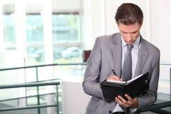 Escritura del hombre de negocios en diario Foto de archivo libre de regalías