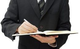 Escritura del hombre de negocios en diario del negocio Imágenes de archivo libres de regalías