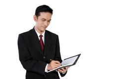 Escritura del hombre de negocios en el cuaderno, aislado en blanco Imágenes de archivo libres de regalías