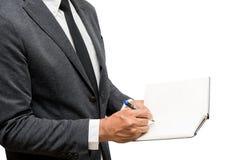 Escritura del hombre de negocios en el cuaderno con el fondo blanco Imagenes de archivo