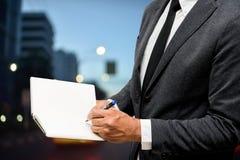 Escritura del hombre de negocios en el cuaderno con la luz de la ciudad Imagenes de archivo