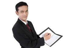 Escritura del hombre de negocios en el cuaderno y mirada a la cámara, aislada Fotos de archivo