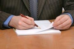 Escritura del hombre de negocios en el papel en blanco fotografía de archivo libre de regalías