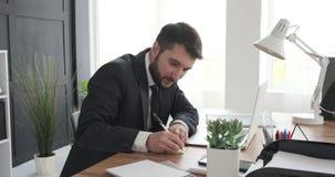 Escritura del hombre de negocios en nota adhesiva y el pegarse en el ordenador portátil almacen de metraje de vídeo