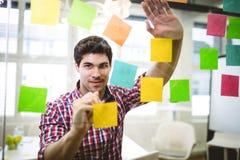 Escritura del hombre de negocios en notas pegajosas coloreadas multi Fotos de archivo libres de regalías