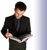 Escritura del hombre de negocios en notebo Imagen de archivo