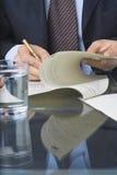 Escritura del hombre de negocios en un documento foto de archivo