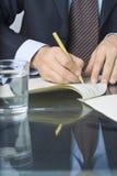 Escritura del hombre de negocios en un documento Imágenes de archivo libres de regalías