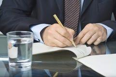 Escritura del hombre de negocios en un documento Imagen de archivo