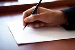 Escritura del hombre en el papel Foto de archivo libre de regalías