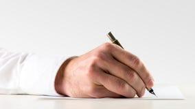Escritura del hombre en la hoja de papel con la pluma Fotos de archivo