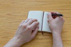 Escritura del hombre en un cuaderno Fotografía de archivo