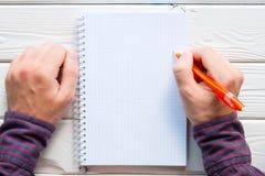 Escritura del hombre en un cuaderno Imagenes de archivo