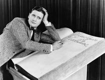 Escritura del hombre joven en un cuaderno de gran tamaño (todas las personas representadas no son vivas más largo y ningún estado Foto de archivo