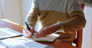 Escritura del hombre mayor en el diario en la cocina 4k metrajes
