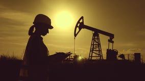 Escritura del ingeniero de la mujer en el tablero en campo petrol?fero Ropa blanca femenina del casco que lleva y de trabajo Indu metrajes