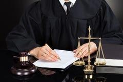 Escritura del juez en el papel en el escritorio fotografía de archivo libre de regalías