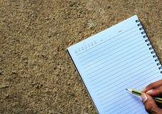 Escritura del lápiz de la manija en el cuaderno Imagen de archivo