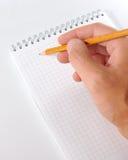 Escritura del lápiz del whith de la mano en cuaderno Imagen de archivo libre de regalías