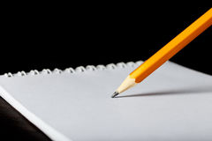 Escritura del lápiz en el primer del Libro Blanco Foto de archivo libre de regalías