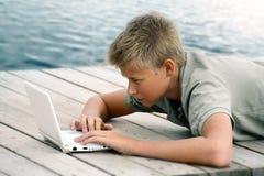 Escritura del muchacho con el ordenador Imagenes de archivo