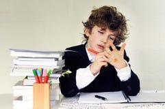Escritura del muchacho de escuela en su mano Foto de archivo libre de regalías