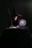 Escritura del muchacho del mago con una pluma Imagenes de archivo