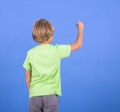 Escritura del muchacho en el backgroung azul Imagenes de archivo