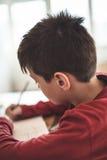 Escritura del muchacho en el cuaderno Foto de archivo libre de regalías