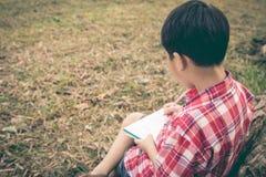 Escritura del muchacho en el cuaderno Concepto de la educación Estilo de la vendimia Imagen de archivo