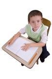 Escritura del muchacho en el escritorio de la escuela Foto de archivo libre de regalías