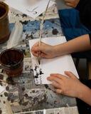 Escritura del niño con una canilla foto de archivo