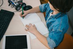 escritura del niño de la opinión de alto ángulo en cuaderno fotografía de archivo libre de regalías