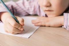 Escritura del niño en cuaderno Imagen de archivo libre de regalías