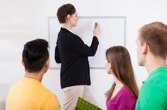 Escritura del profesor en whiteboard en la sala de clase Foto de archivo