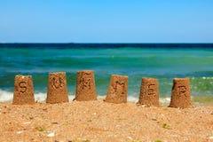 Escritura del verano en torres de la arena fotos de archivo libres de regalías