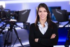 Escritura e información de noticias Periodista de la mujer en el estudio de la televisión que se coloca con sus brazos cruzados Imagen de archivo libre de regalías