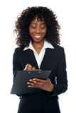 Escritura ejecutiva femenina africana en la libreta fotos de archivo