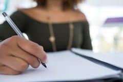 Escritura ejecutiva femenina en un documento en el escritorio en la oficina Foto de archivo libre de regalías