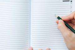 Escritura en el cuaderno foto de archivo libre de regalías