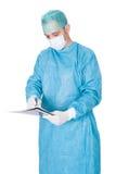 Escritura en funcionamiento del doctor vestido en carpeta Foto de archivo libre de regalías