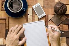 Escritura en la hoja de papel en blanco en la textura de madera Fotografía de archivo libre de regalías
